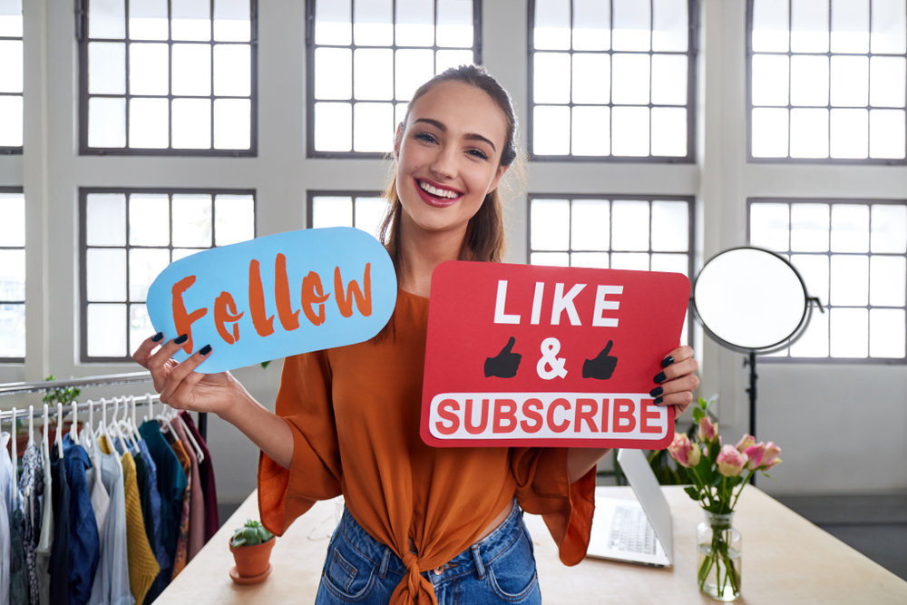"""Mädchen hält zwei Schilder vor ihrem Körper. Eines mit der Aufschrift """"Follow"""" und eines mit """"Like&Subscribe""""."""