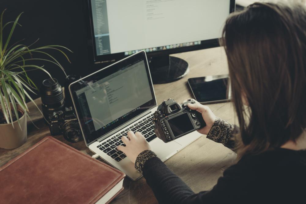 Frau hält Kamera in der rechten Hand und tippt mit der Linken auf dem Laptop