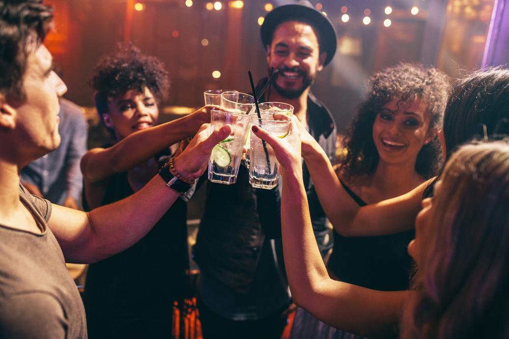 Junge Leute stossen an in einer Bar